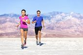 Постер, плакат: Runners trail running on dry desert landscape Couple of fit athletes sprinting in compression activ