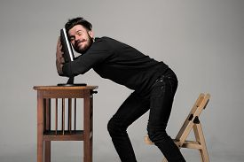 foto of hug  - Funny and crazy man using a computer on gray background - JPG