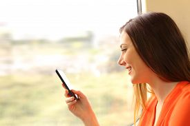 stock photo of passenger train  - Passenger using a mobile phone in a train or bus beside the window - JPG