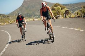 picture of triathlon  - Cyclist riding bikes on open road - JPG
