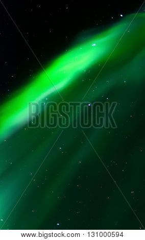 The green glow of an aurora rises like a curtain up the sky.