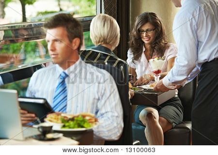 Young woman sitting in cafe, waiter serving sweets. Businessman eating club sandwich and working in the forground. Selective focus on women.