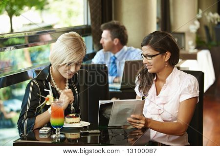Young women sitting in cafe having sweets, looking at magazine.