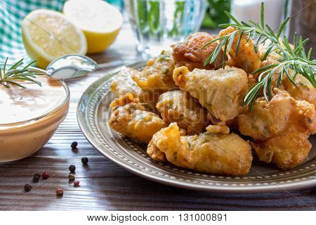 In foreground shrimps in crispy dough on a plate with rosemary and bowl of sauce near, in background glass of water, lemon, herbs, salt, pepper. Shrimps in pastry and sauce. Horizontal. Close.