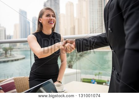 Two business people shaking hands on a meeting. selective focus on the shaking hands