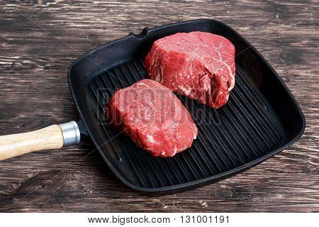 Fresh Raw Beef steak Mignon on grilled pan.