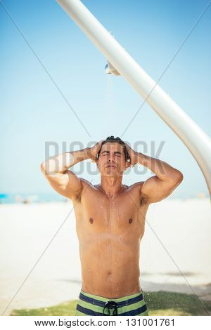 Handsome man taking a shower on the beach.