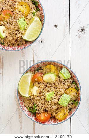 Quinoa with tomatoes, zucchini and lime on white wooden table