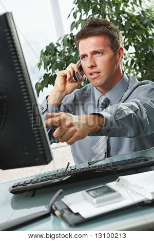 Troubled businessman pointing at screen disussing work on mobile phone sitting at office desk.