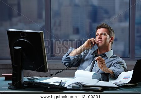 Mid-adult successful smiling businessman calling on landline listening to conversation sitting at office desk.