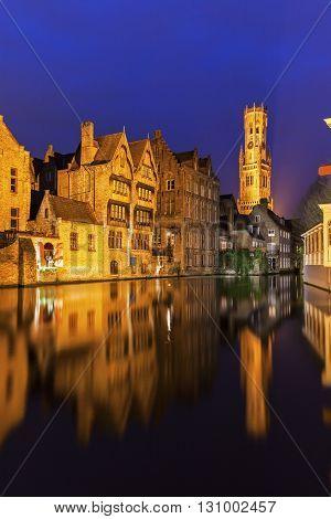 Belfry of Bruges reflected in the canal. Bruges Flemish Region Belgium