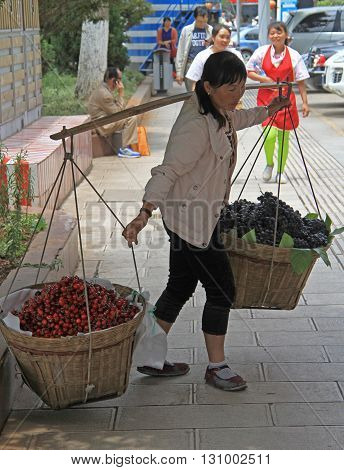 Woman Is Carrying Two Backets With Cherries And Grapes