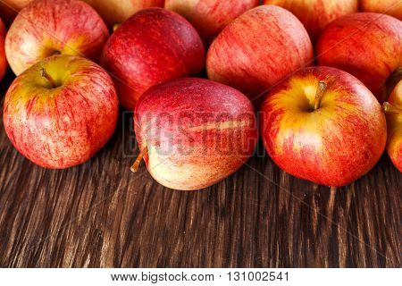 close up of fresh apples on wooden background.