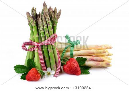 Green and white asparagus with strawberries. Fresh healthy vegetables on white background.