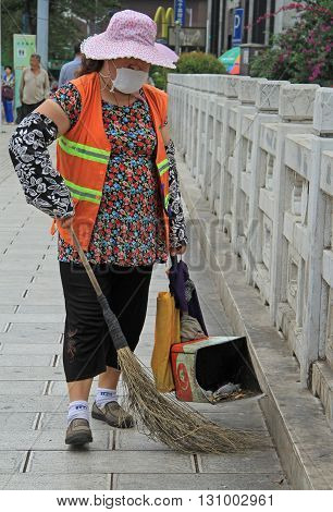 Woman Is Cleaning Up The Street In Kunming, China
