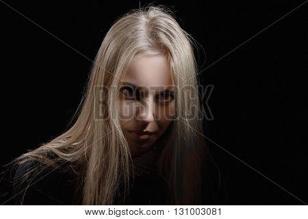 sad pensive blond girl on black background