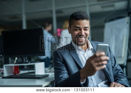 Happy african american businessman using a mobile phone in an office.