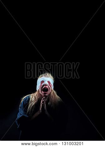 wounded scared bloody girl screaming on black background with copyspace