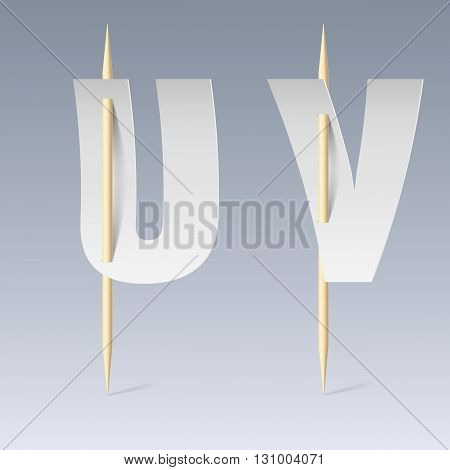 White paper cut font on toothpicks on grey background. U and V letters