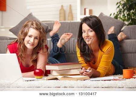 Happy teen girls lying on floor with laptop and books smiling at camera at home.