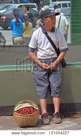 Man Is Selling Cherries On The Street In Kunming, China