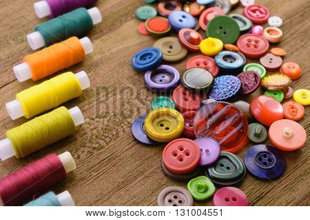 macro handful of multi-colored buttons for clothes near multi-colored threads on reels for sewing. wooden background