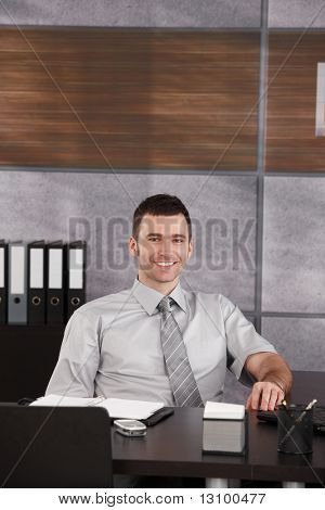 Portrait of casual businessman sitting at desk wearing short sleeved shirt, smiling. Copyspace above head.