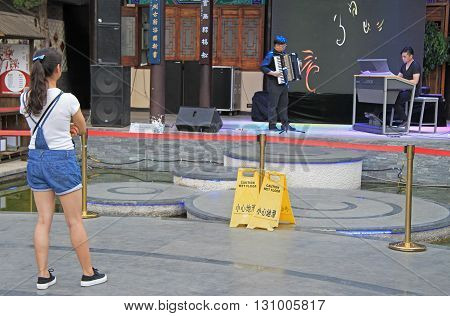 Girl Is Watching A Performance In Kunming, China