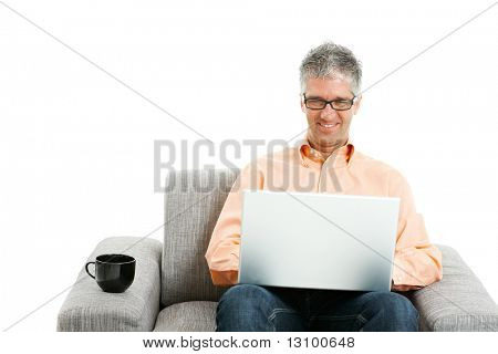 Mid-adult man wearing jeans and orange shirt sitting on couch, using laptop computer. Isolated on white.
