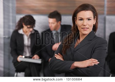 Portrait of confident mid-adult businesswoman standing on office lobby, smiling.