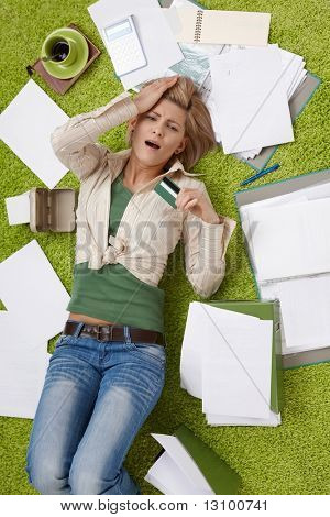 Shocked woman lying on living room floor surrounded with bills, holding credit card, with hand on forehead in high angle view.