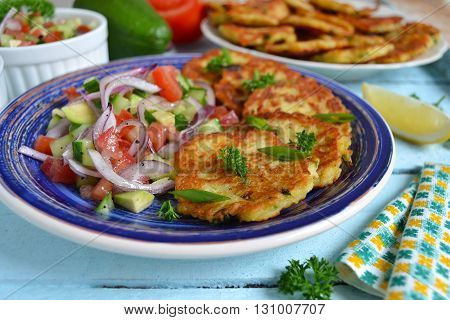 potato pancakes with green onions and sour cream on a wooden background