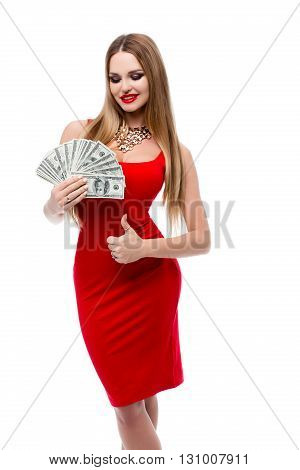 Insanely beautiful young woman in red dress holding a lot of 100 dollar bills and showing thumbs up all okay. Fashionable girl in red evening dress with bright makeup and red lips