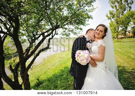 Groom Kissing Neck Of Bride Background Landscape With River