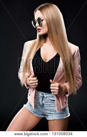 Fashionable stylish woman in denim outfit and a beautiful coat looking to the side at the mirrored sun glasses. The girl's red lips. Studio photo on a black background