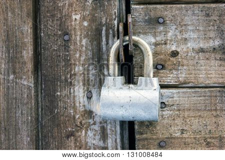 Old rusty painted metal padlock on wooden board door of shed closeup