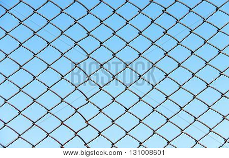 a fence of metal wire on a background of blue sky.