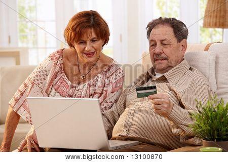 Casal de idosos compras on-line em casa, usando computador portátil e cartão de crédito.