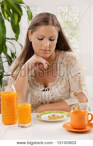 Young woman on diet sitting at table, thinking over tape measure on plate.