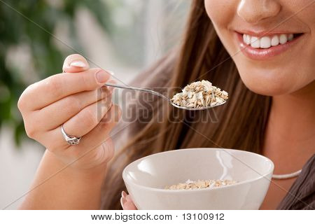 Closeup of partially visible young woman eating breakfast cereal. Selective focus on spoon.