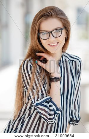 Portrait of happy woman in glasses in spring city,blonde long straight hair,blue eyes,beautiful white teeth and nice smile,light makeup,wearing a thin striped blouse with white and black stripes,spends time in the city enjoying the Sunny day