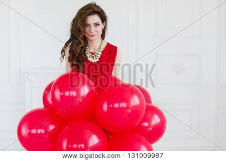 Young beautiful brunette woman with long curly hair and grey eyes,dressed in a red sleeveless dress,round neck wears a white necklace, a portrait, on light gray background in the Studio with a bunch of red balloons on my birthday