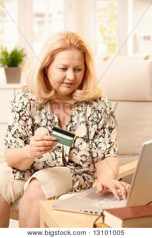 Elderly woman using computer for electronic shopping, typing on keyboard, holding creditcard, sitting in armchair.