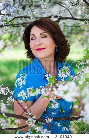 Happiness Concept - Portrait Of Middle Aged Woman Posing In Cherry Garden