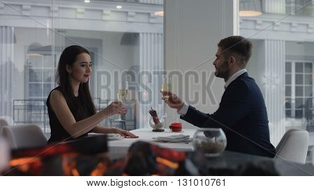 Young happy amorous couple with glasses of champagne on romantic date at restaurant