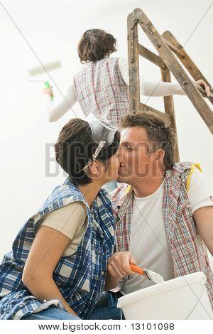 Casal se beijando em casa renovação, segurando o pincel, amiga de pé na escada pintando wa