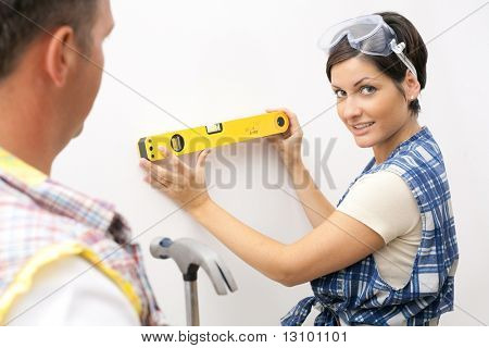 Smiling woman in focus holding spirit level, looking at camera, man holding hammer.