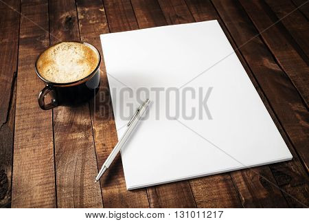 Blank branding template on vintage wooden table background. Letterhead coffee cup and pen. Photo of blank stationery. Mock-up for design portfolios.