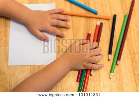 Child drawing by top view Colorful pencils and paper for children artwork