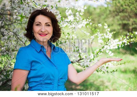 Middle Aged Woman Holding Something In Blooming Garden - Copy Space
